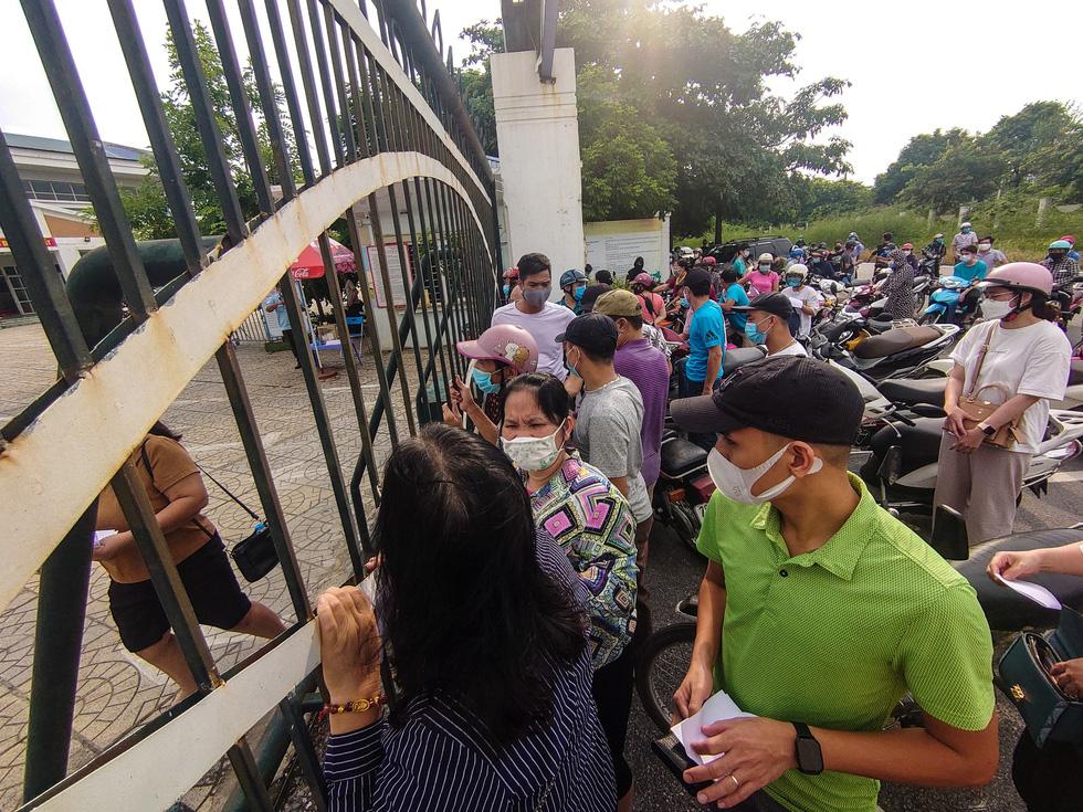 Người dân chen chúc chờ nộp phiếu tiêm chủng - Ảnh: NAM TRẦN